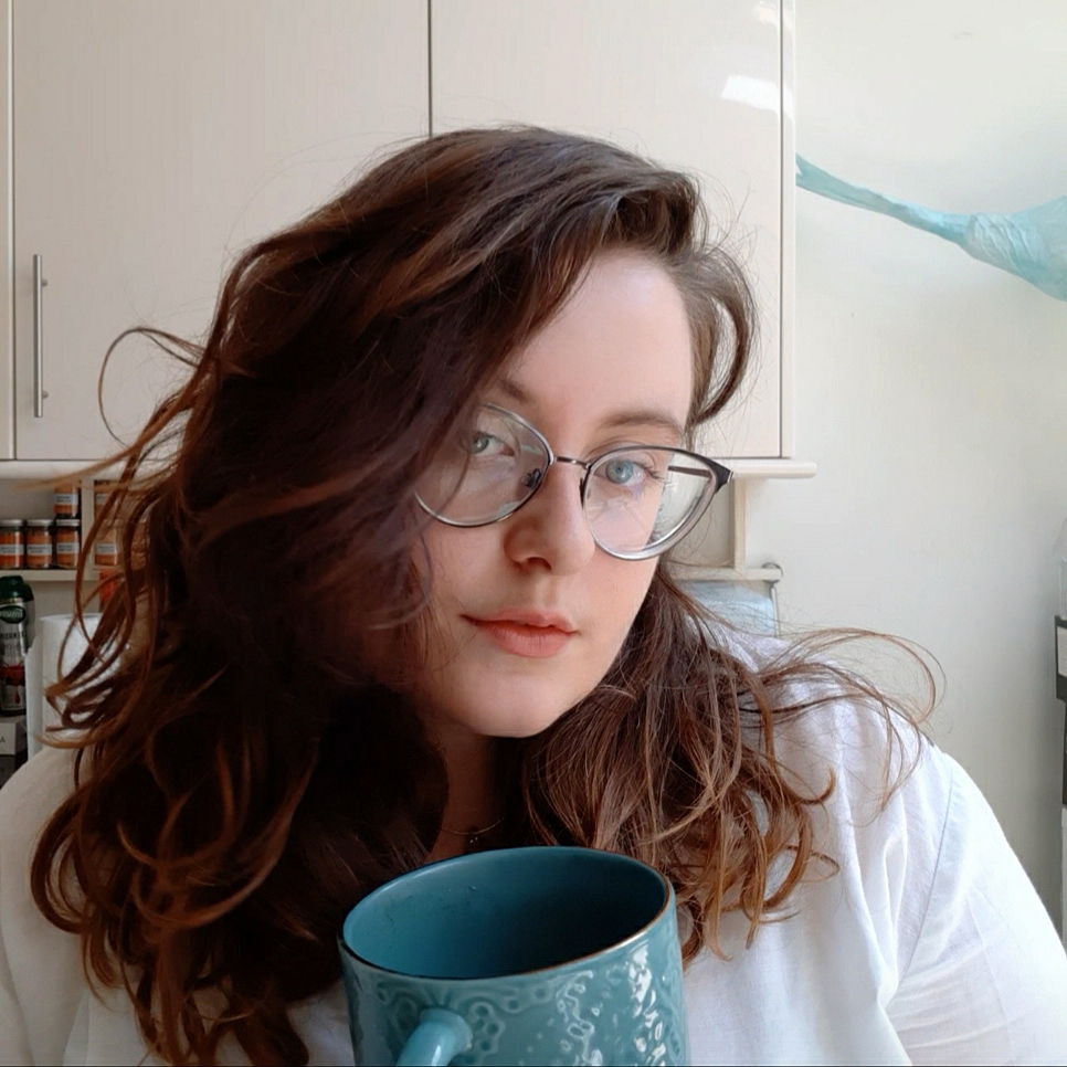 Rosie looking at the camera, holding a blue mug