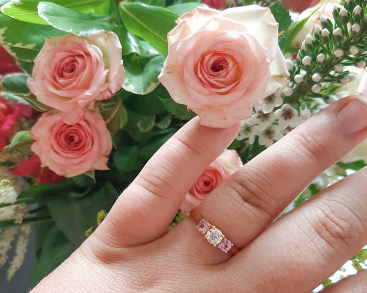 Rosie's hand with a gold engagement ring, with a diamond surrounded by 2 pink sapphires. She is wearing it infront of pink roses