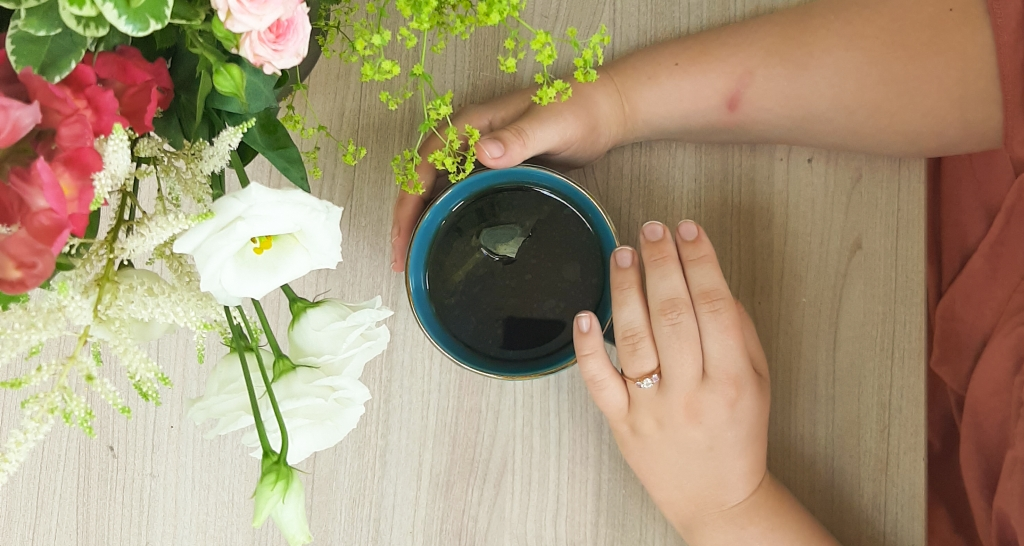 Flaylay of Rosie's hand around a blue mug, whilst she wears her engagement ring. There are pink and white flowers on the left.