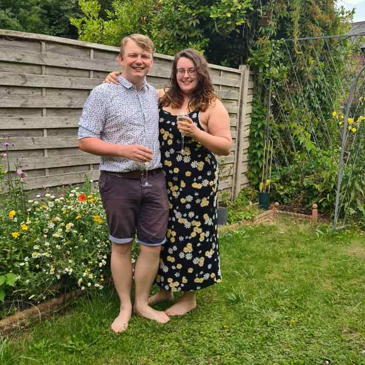 Rory and Rosie stood next to each other in the garden - thy are both holding glasses of champagne.