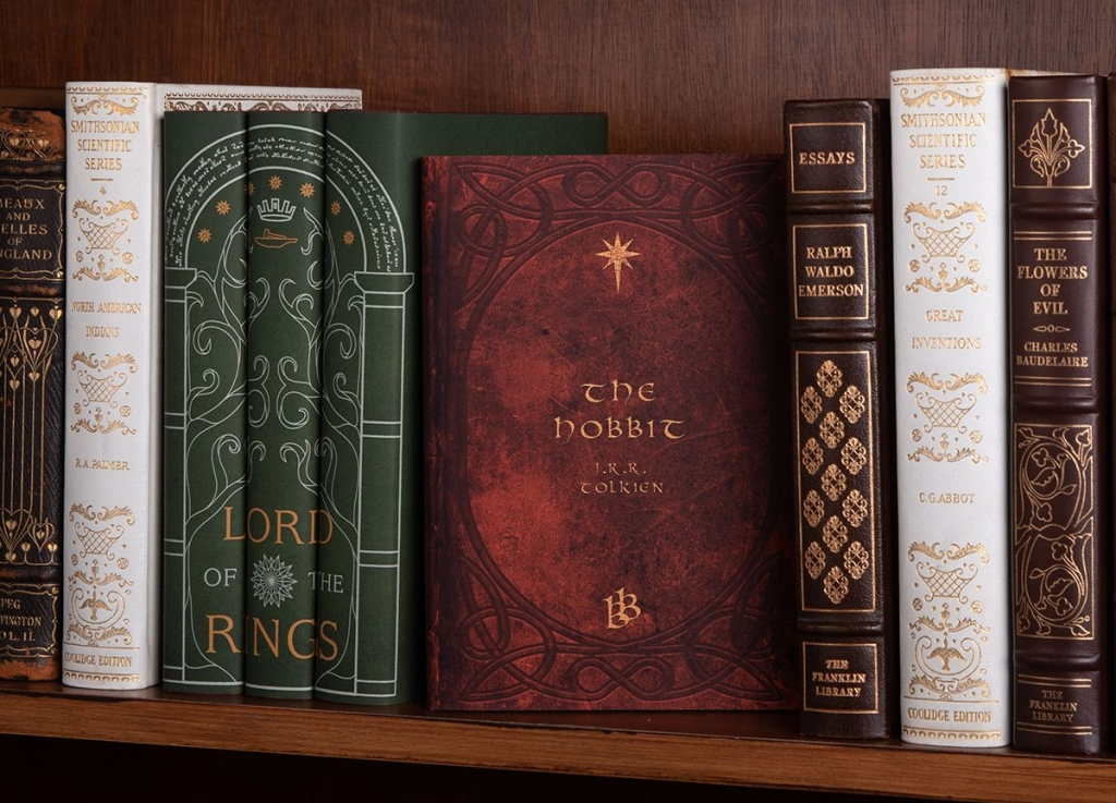 A dark brown shelf with a few books. At the from is a green cover trilogy of Lord of the Rings, and a red covered 'The Hobbit'