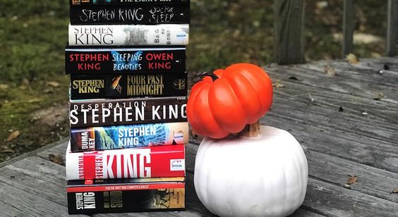 A stack of King's books, next to a pumpkin and a white gourd