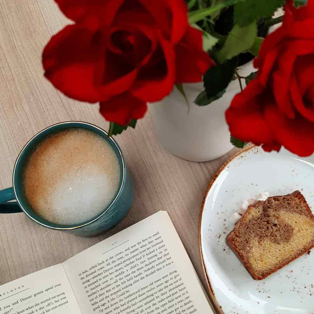A frothy cup of coffee, a slice of cake, and a book open flat. Red roses are in the top right corner, out of focus.