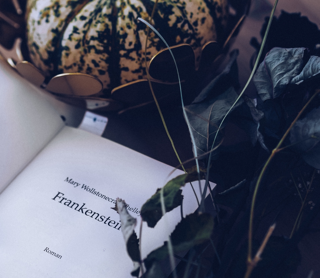 A page of Frankenstein amongst green foliage and a white dappled gourd