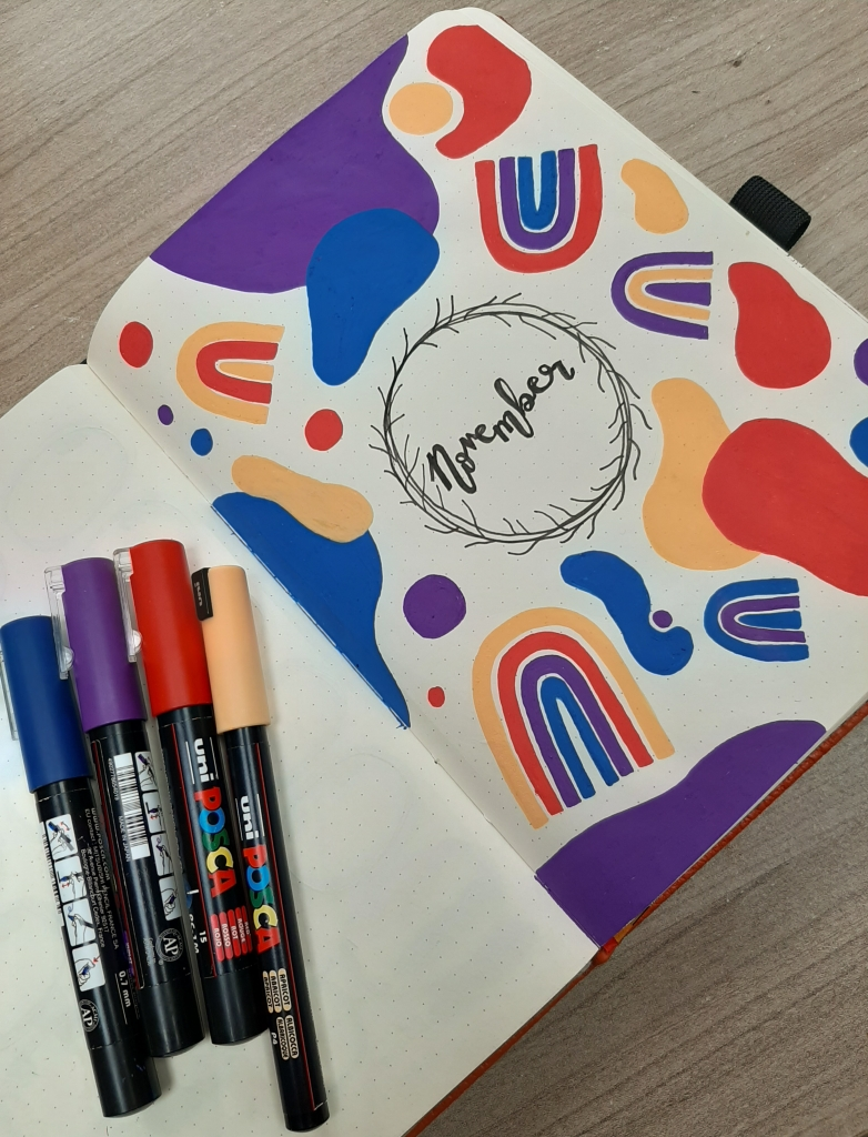 Close up of the November bullet journal header page. Blue, purple, red, and orange Posca Pens are off to the left