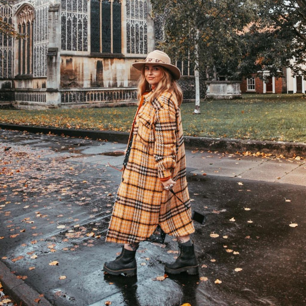 Helen is wearing a long, yellow check winter coat, black stomping boots, and a tan wide brim hat. She is walking forward and looking at the camera