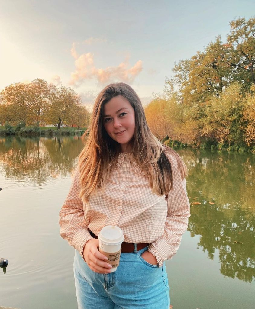 Lucy is wearing a pale pink check shirt, and blue mom jeans. She is posing in front of an autumn lake scene and looking directly at the camera.