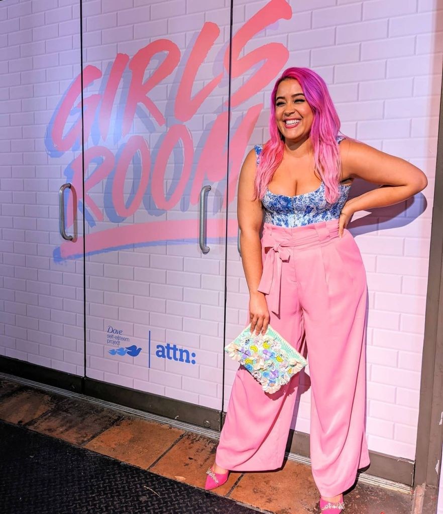 Megan is wearing bright pink trousers and blue corset top, and is accessorising with hot pnk shoes and a floral clutch. She is smiling to the right, behind a sign that says Girls Room