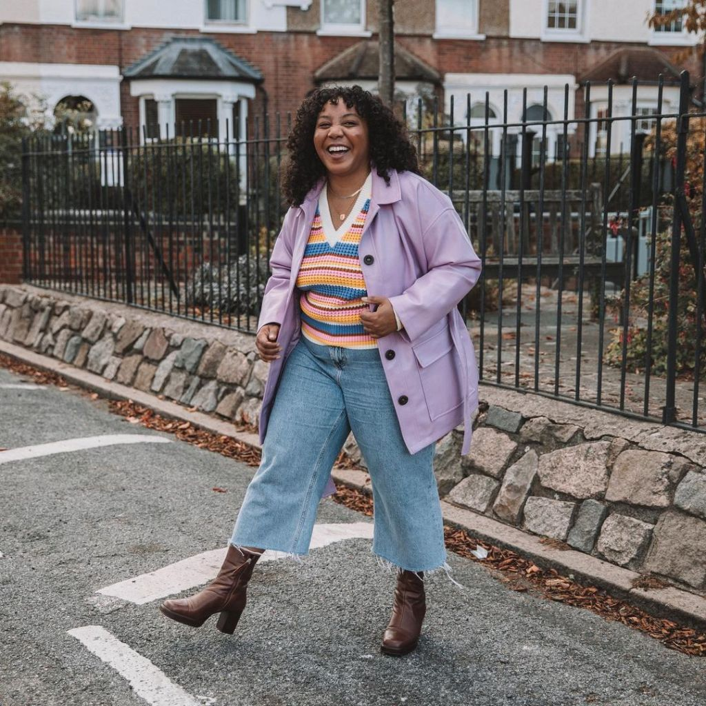 Nicole is wearing a pastel lilac jacket, orange and blue striped jumper, and light blue cropped jeans. She has one foot kicked forward and is grinning towards the camera