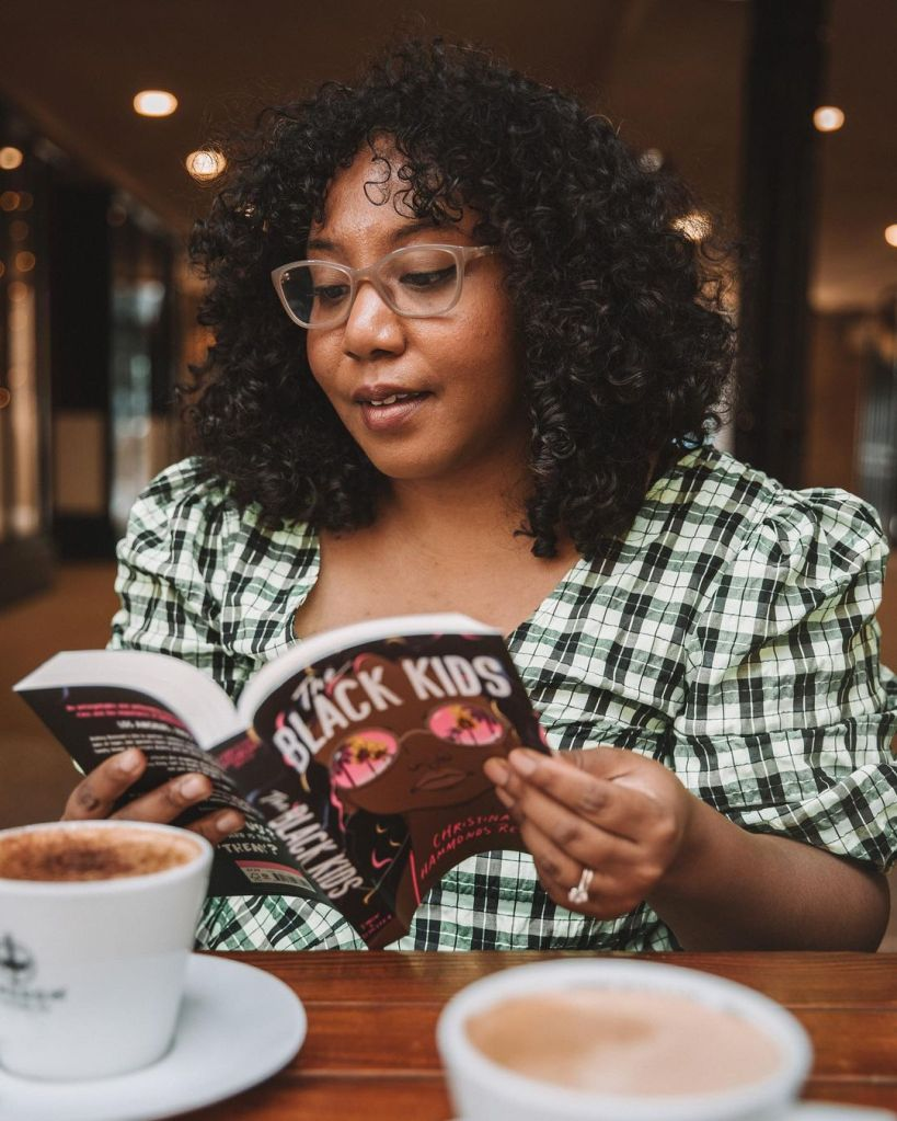 Nicole is wearing a black and white check puff sleeve top, and tan glasses. She is reading a novel called 'The Black Kids', and there's coffee in the foreground