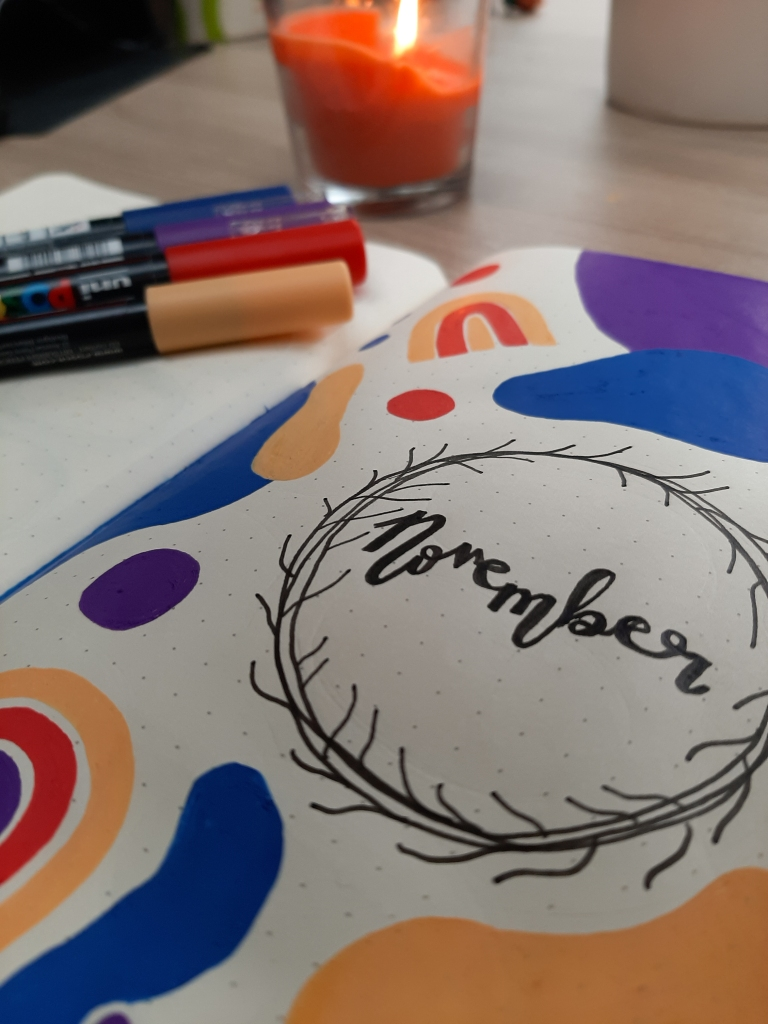 """""""November"""" written in calligraphy, surorunded by primary colour doodles. Four Posca pens are in the background."""