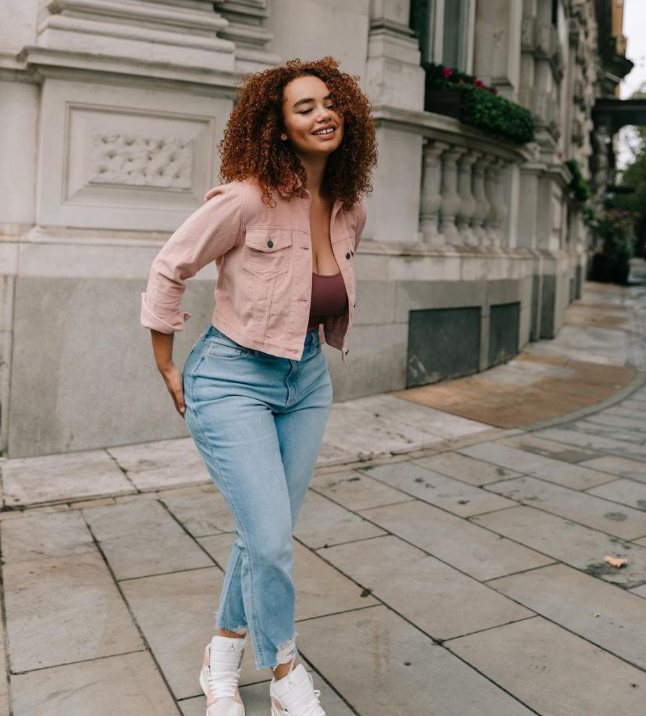 Sonny is wearing light blue mom jeans, a dark pink vest, and a light pink cropped denim jacket. Her eyes are closed, she is smiling, and has her hands behind her.