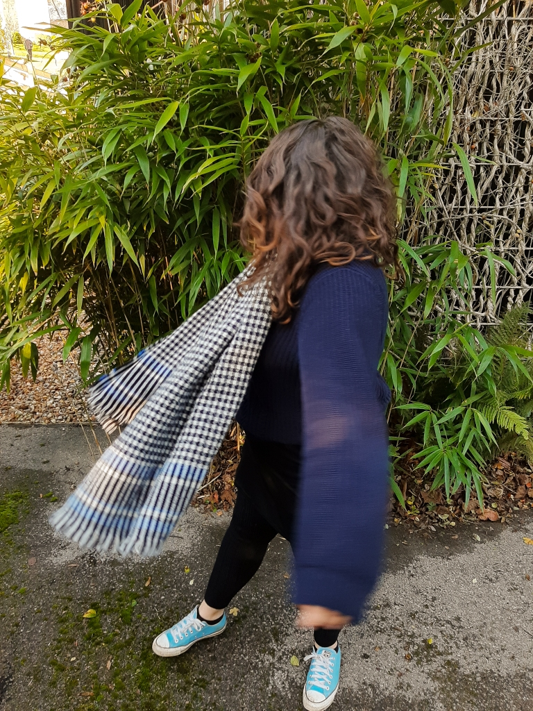 Rosie is wearing a blue jumper, and is spinning away from the camer.a. She is wearing a white and black checkered scarf, and is against a background of green foliage