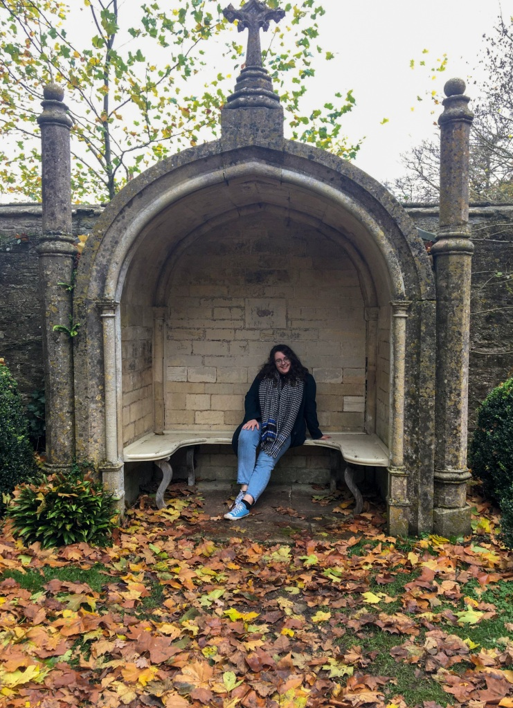 Rosie is sat in on a grey stone bench, surrounded by yellow leaves