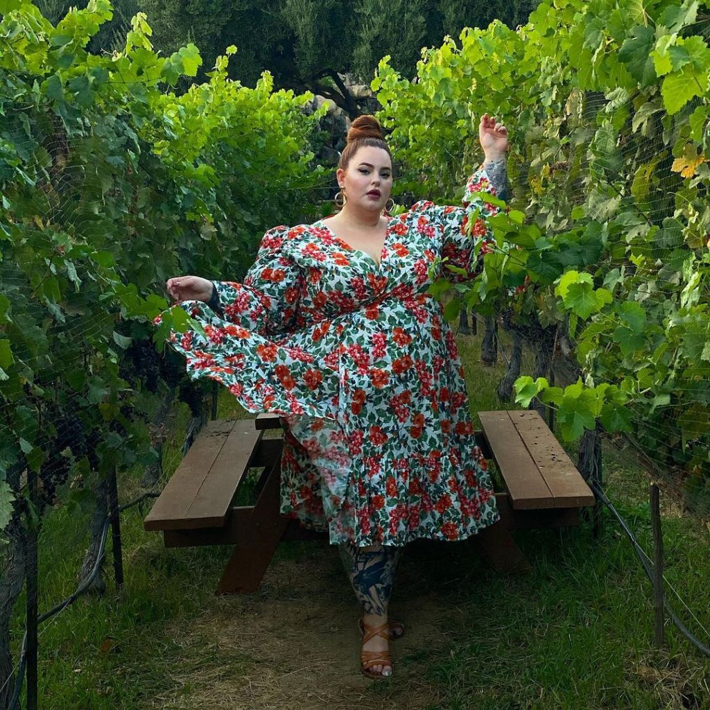 Tess is wearing a red, green, and white midi dress, and is flinging up a corner of the skirt. She is posing in a green vineyard, and is looking directly at the camera.
