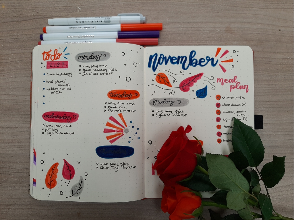 Jewel toned weekly spread, with drawings of leaves. Red and orange roses lay on the page.