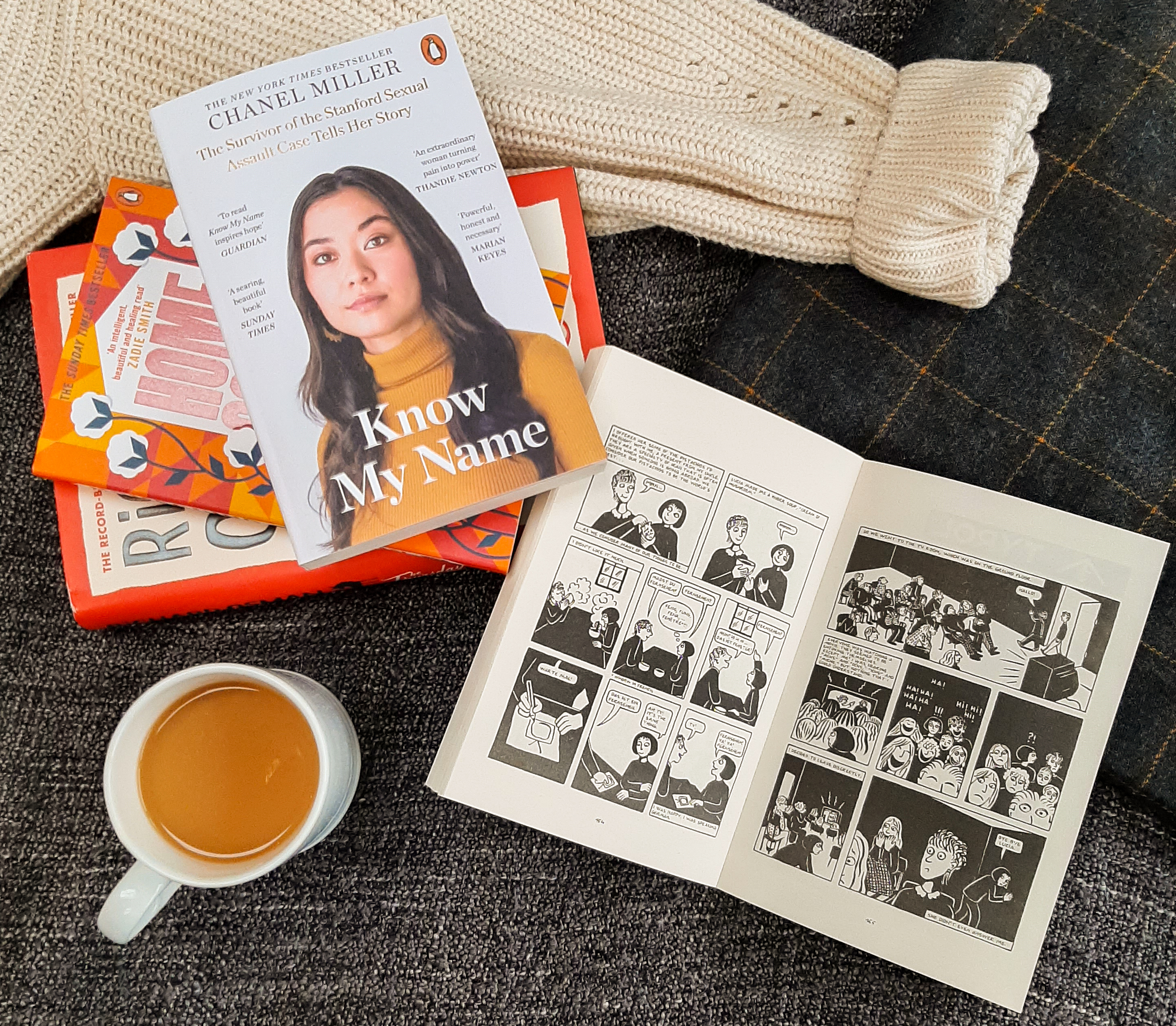Cup of tea in a white mug, bottom left. Top right, a stack of orange and white books.