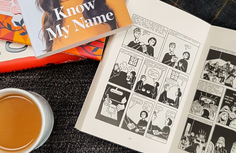 White and orange books on a grey background. A white jumper arm peeks through on the left. Rosie's hand holds a cup of tea in a white mug.