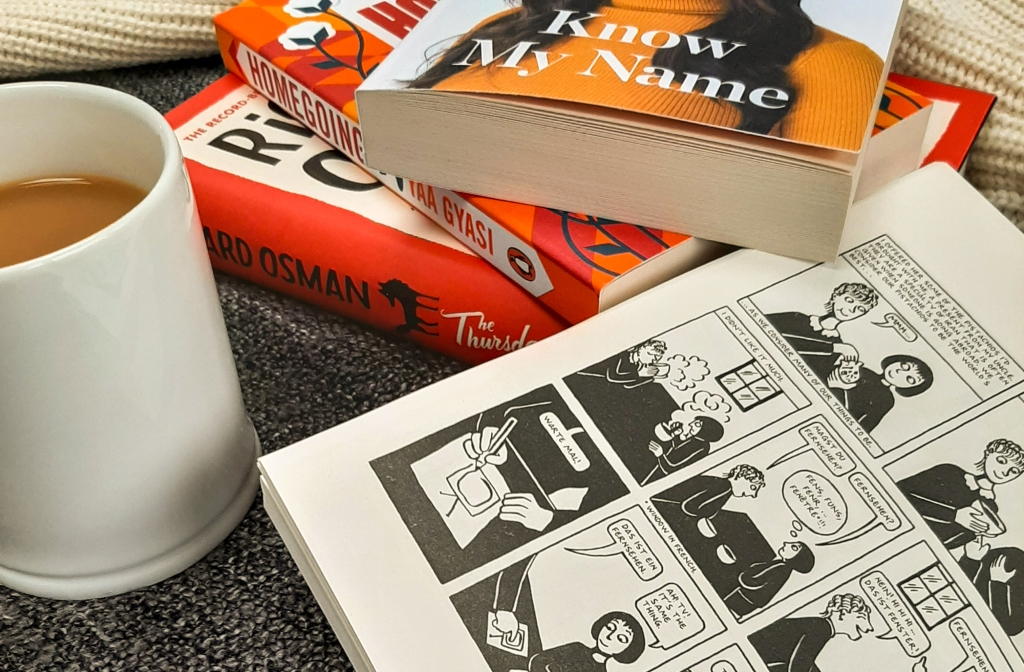 White mug filled with milky tea. Three red/orange toned books in the background. Black and white graphic novel lays open.