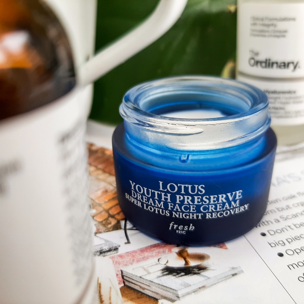 A blue tub of Fresh's Lotus Youth Preserve Dream Face Cream. It is on a white and black background.