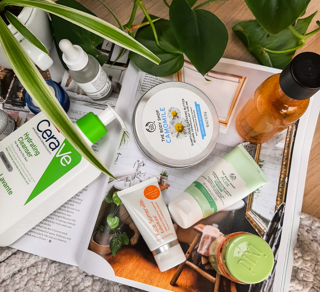A collection of cruelty-free skincare products on a magazine. There's green plants on the top of the picture, and a white blanket at the bottom