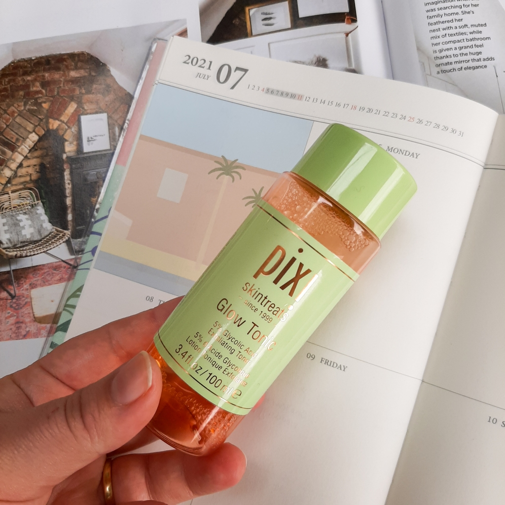 A pink and green bottle of Pixi's Glow Tonic, against a background of a cream diary and white magazine