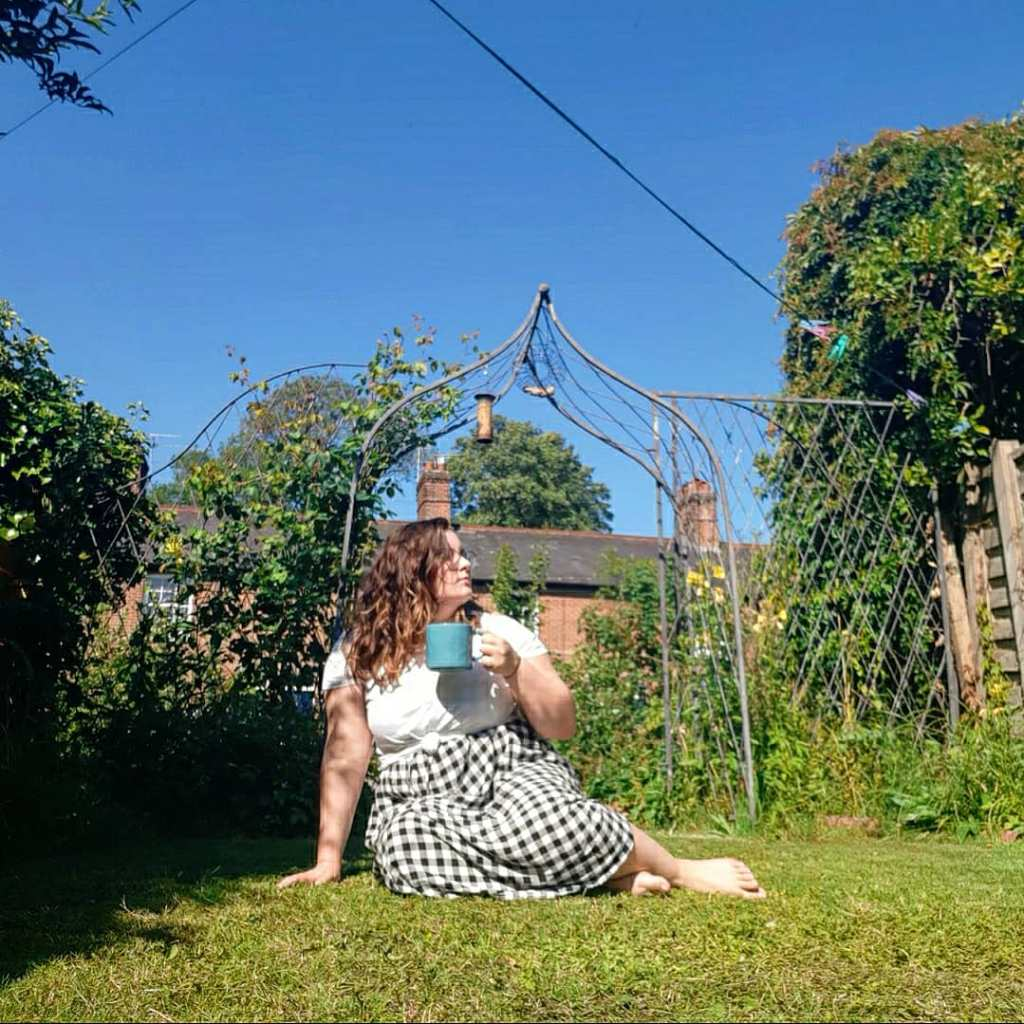 Rosie is sat on green grass, holding a blue mug, and is looking to the left. She is wearing a white tee and black and white checked midi skirt