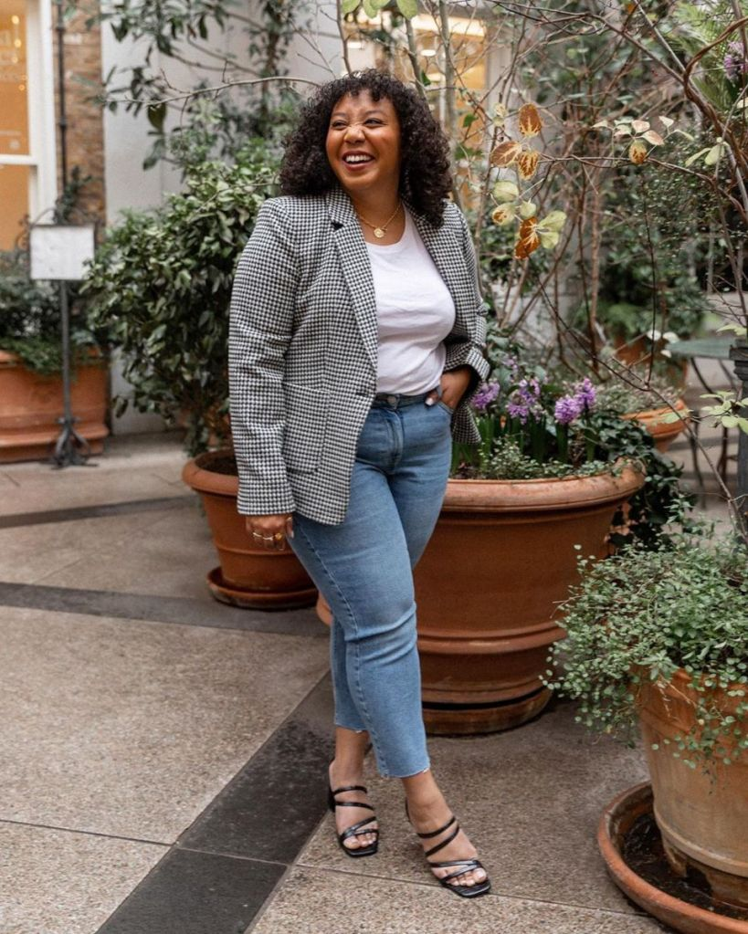 Nicole is wearing a grey check blazer, white tee, blue jeans, and black strappy heels. Nicole has dark hair, and is a mixed-raced, American, size 16 woman.