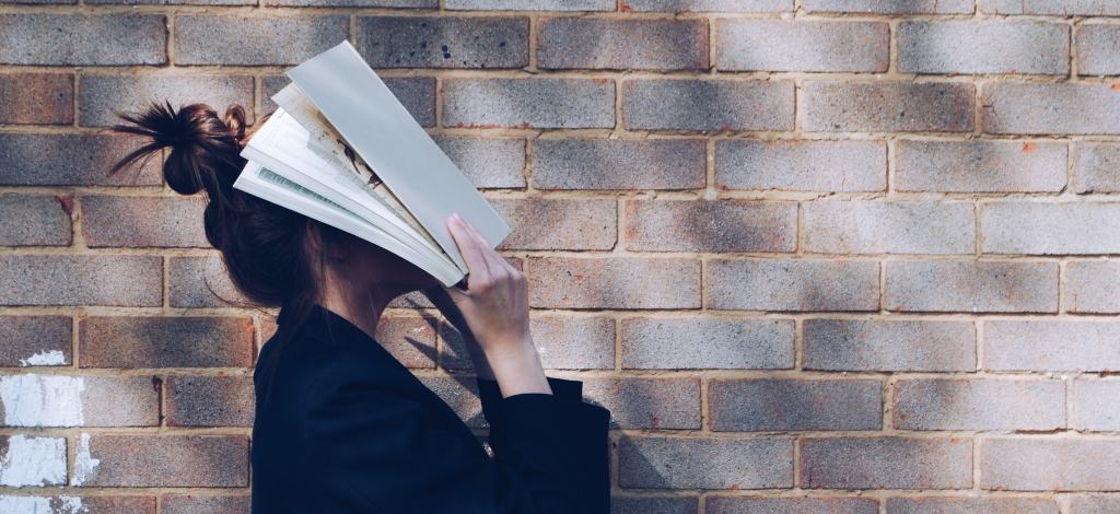 A girl with a messy bun and black blazer, hitting herself in the face with a stack of paper. The brick wall behind her is grey.