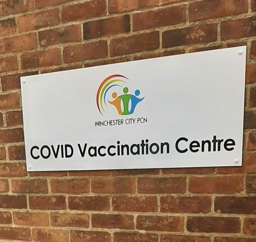A red brick wall, with a white sign that says 'COVID Vaccination Centre' on it in black text.