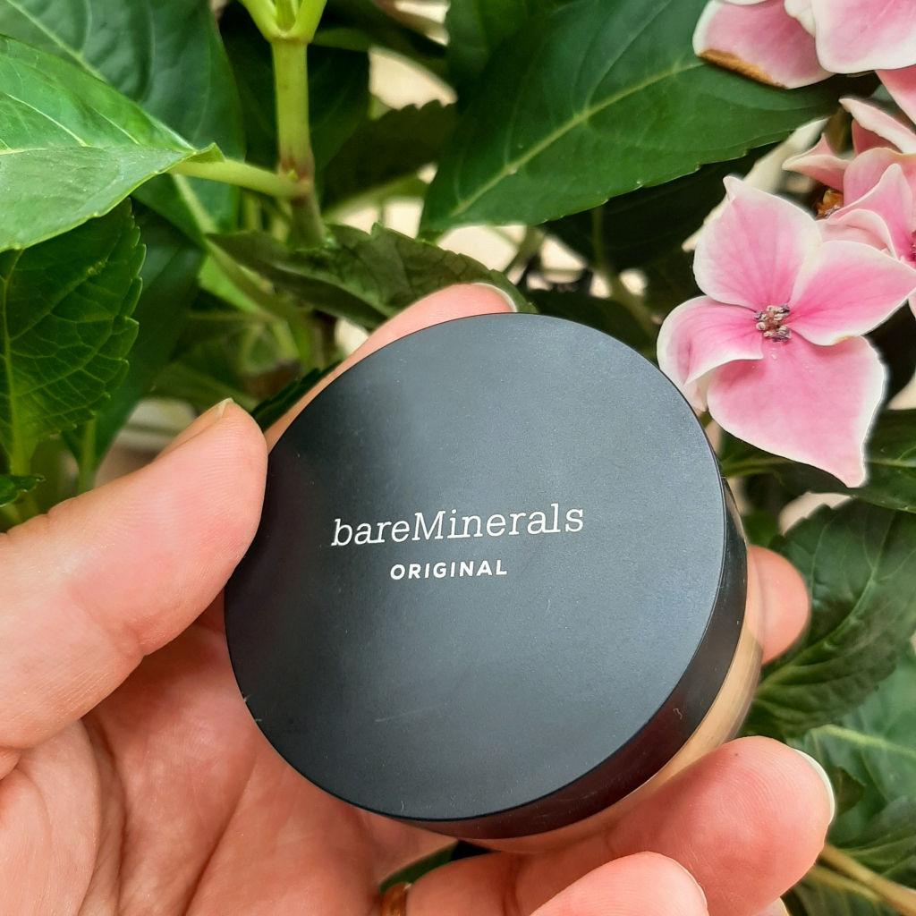 Round foundation container with a black lid that says 'bareMinerals original'. It is held up by Rosie's Caucasian hand against green leaves and pink flowers