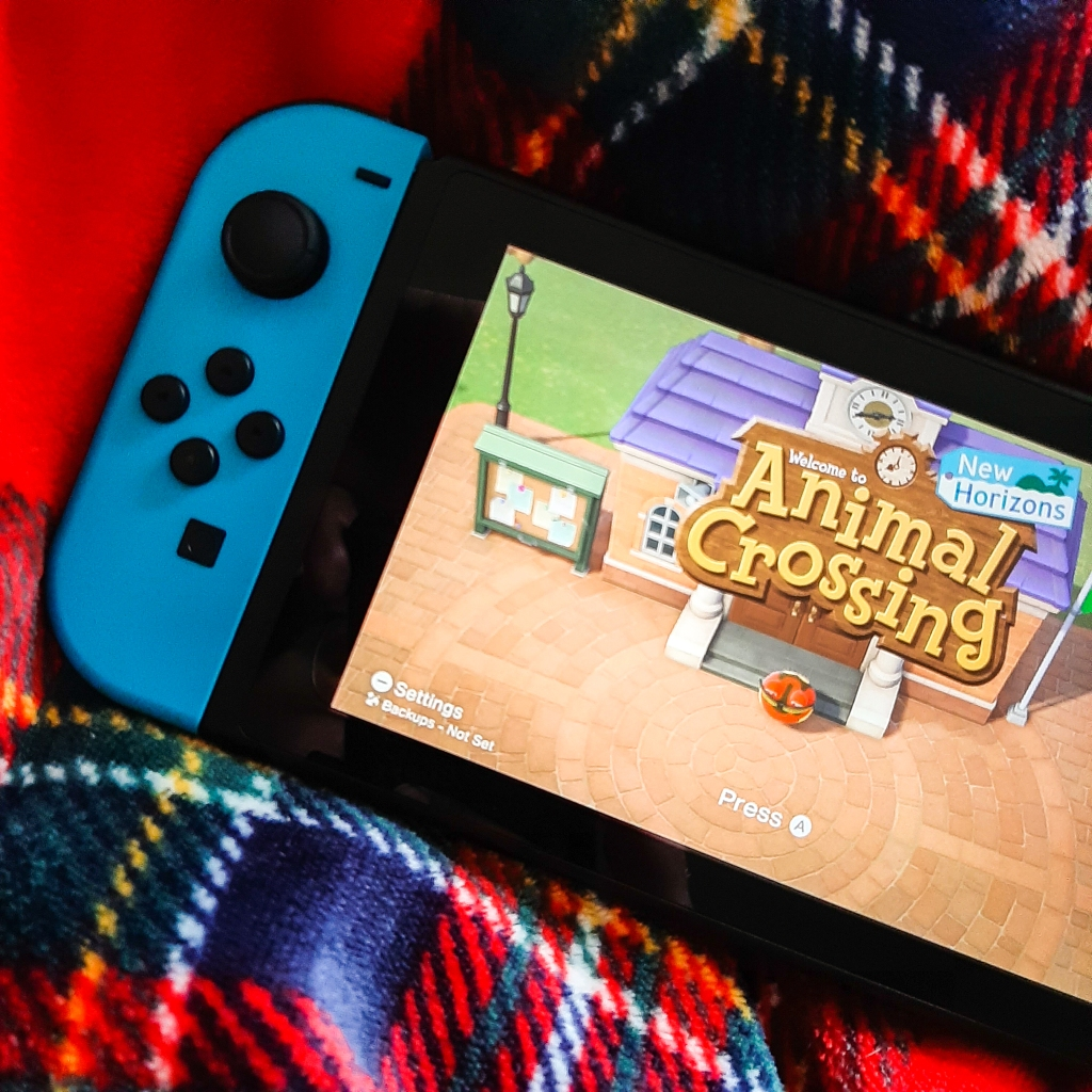 The screen of a Nintendo Switch saying 'Animal Crossing'. The left joycon is blue. It is resting on a red and black blanket.