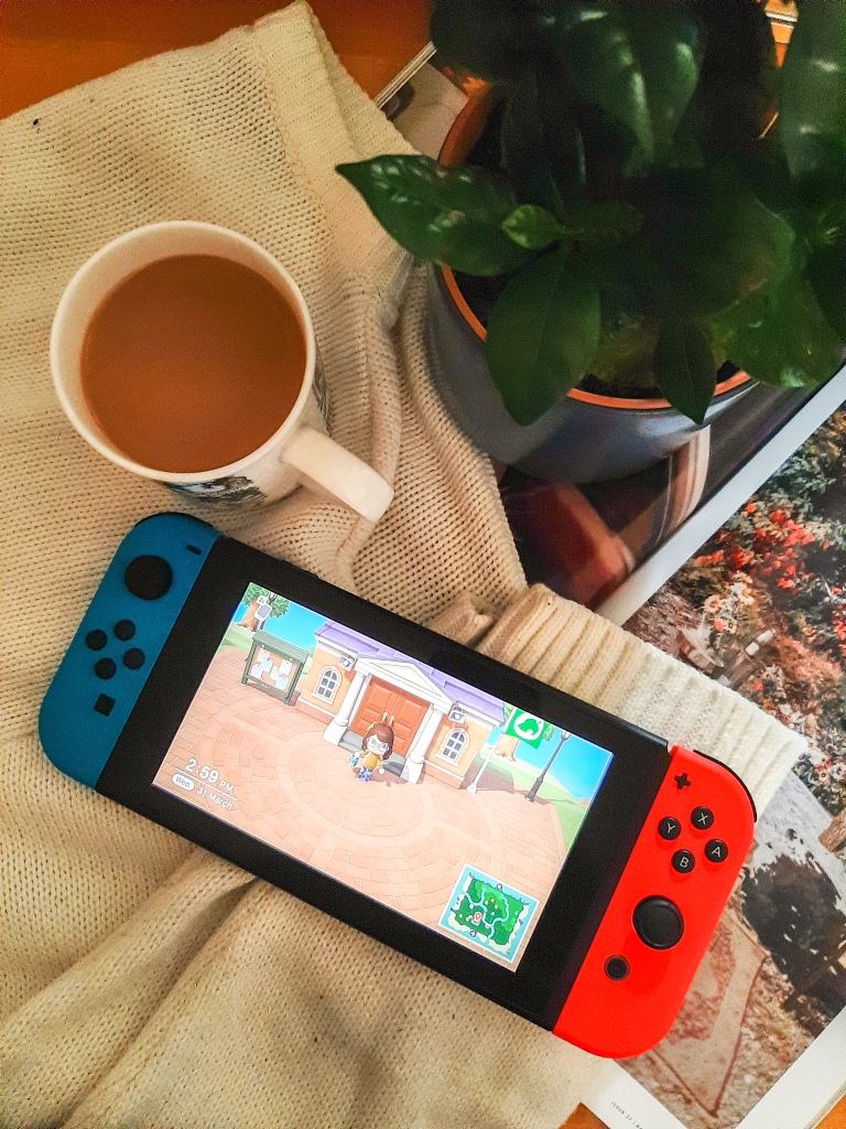 A green plant, white mug with tea, and a cream jumper. On top, is a red and blue Nintendo Switch with Animal Crossing on the screen.