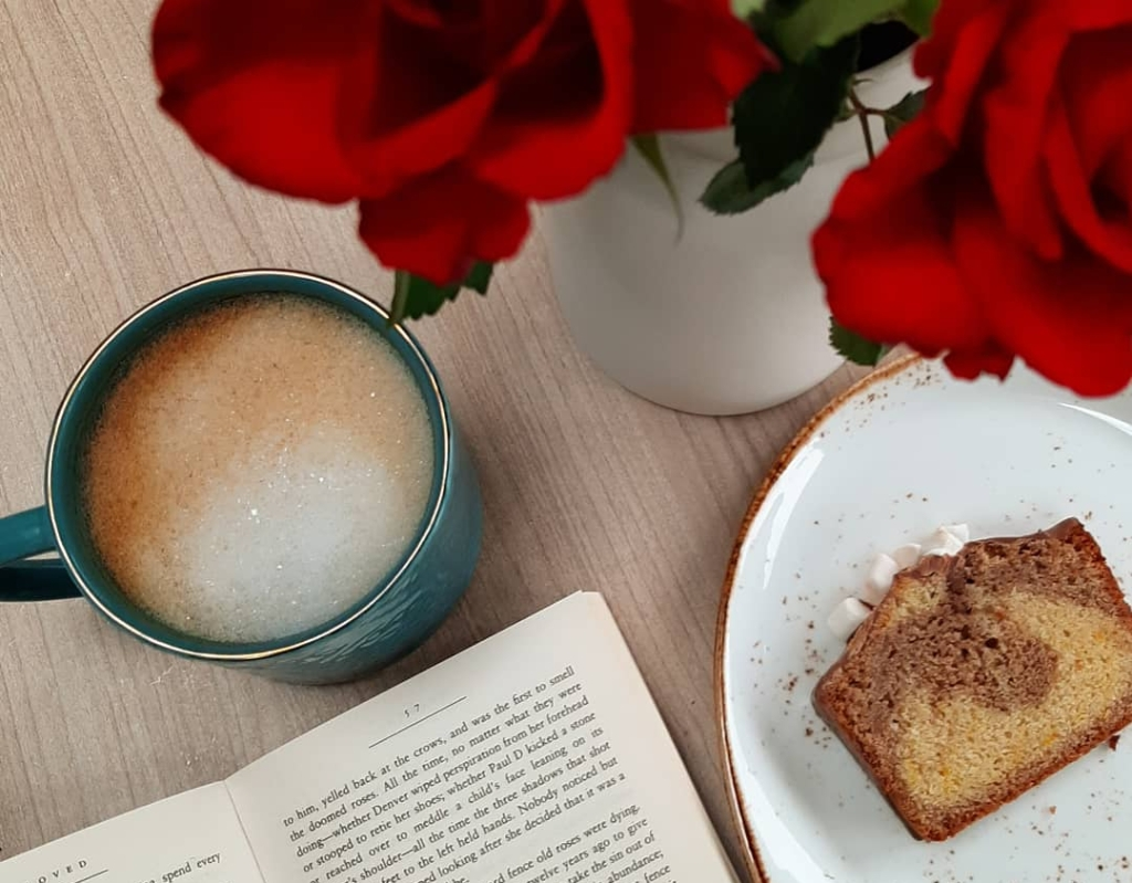 A frothy coffee in a teal mug, next to a white and brown slice of cake. There are red roses