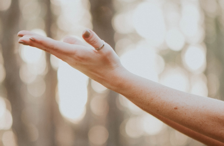 A caucasian hand stretching out, against a blurry background of brown trees