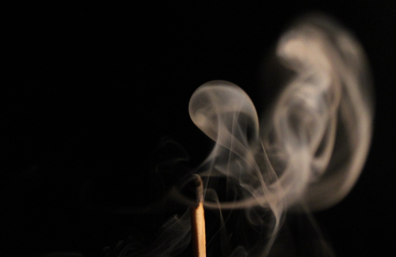 A black background, with a match in the foreground. The match tip is black, and smoke is coming from it.