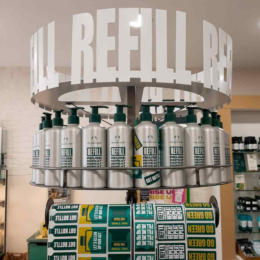 A row of silver bottles with green decal. The word 'REFILL' is above in white. There's a row f green, yellow and white stickers below.
