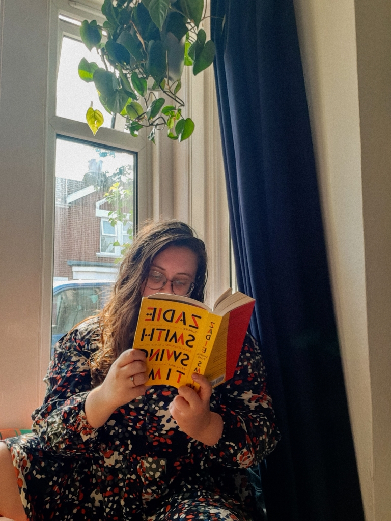 Rosie is sitting in a white window nook, next to a navy curtain. She has dark hair, glasses, and is looking down at a book. She is holding the yellow book in her hands - it is Zadie Smith's Swing Time.