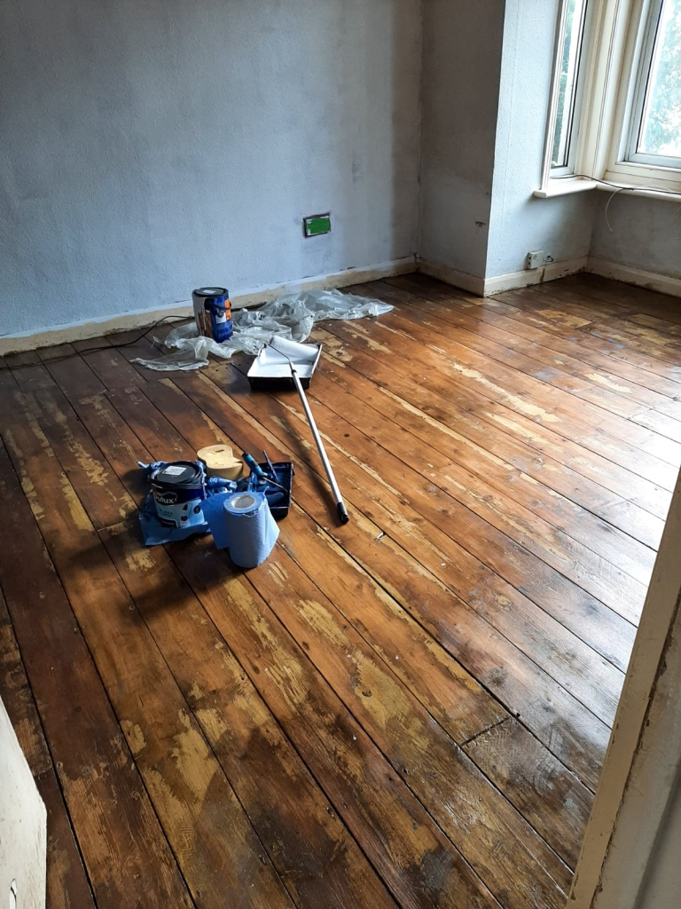 White painted walls, light brown wooden floor, with a paint roller and blue roller
