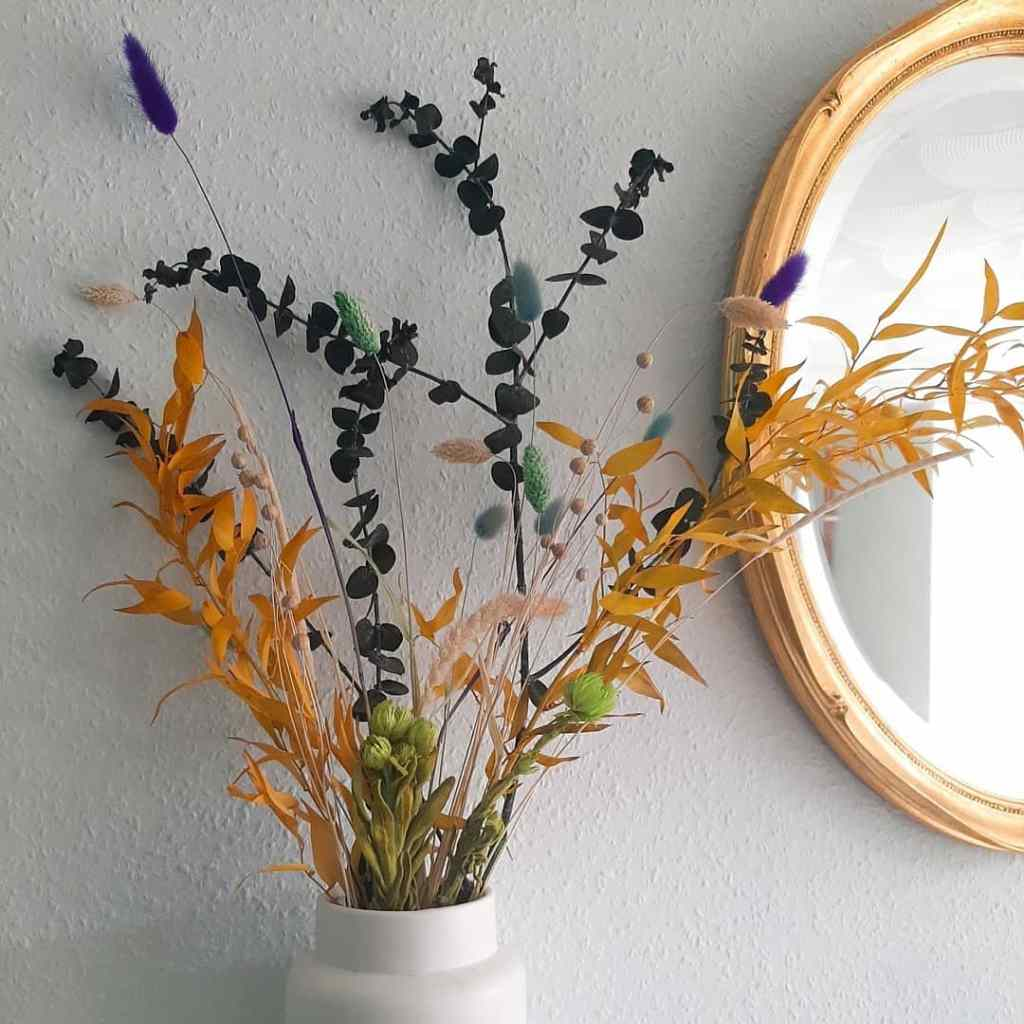 Dried flowers in green, yellow, and blues infront of a white wall and gold gilded mirror