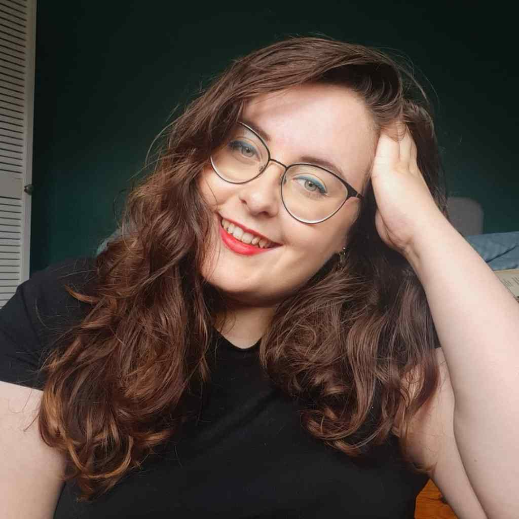 Rosie, a caucasian woman with brunette wavy hair, is looking at the camera with a hand in her hair. She is wearing a black t-shirt, had black glasses, red lips, and blue eyeliner