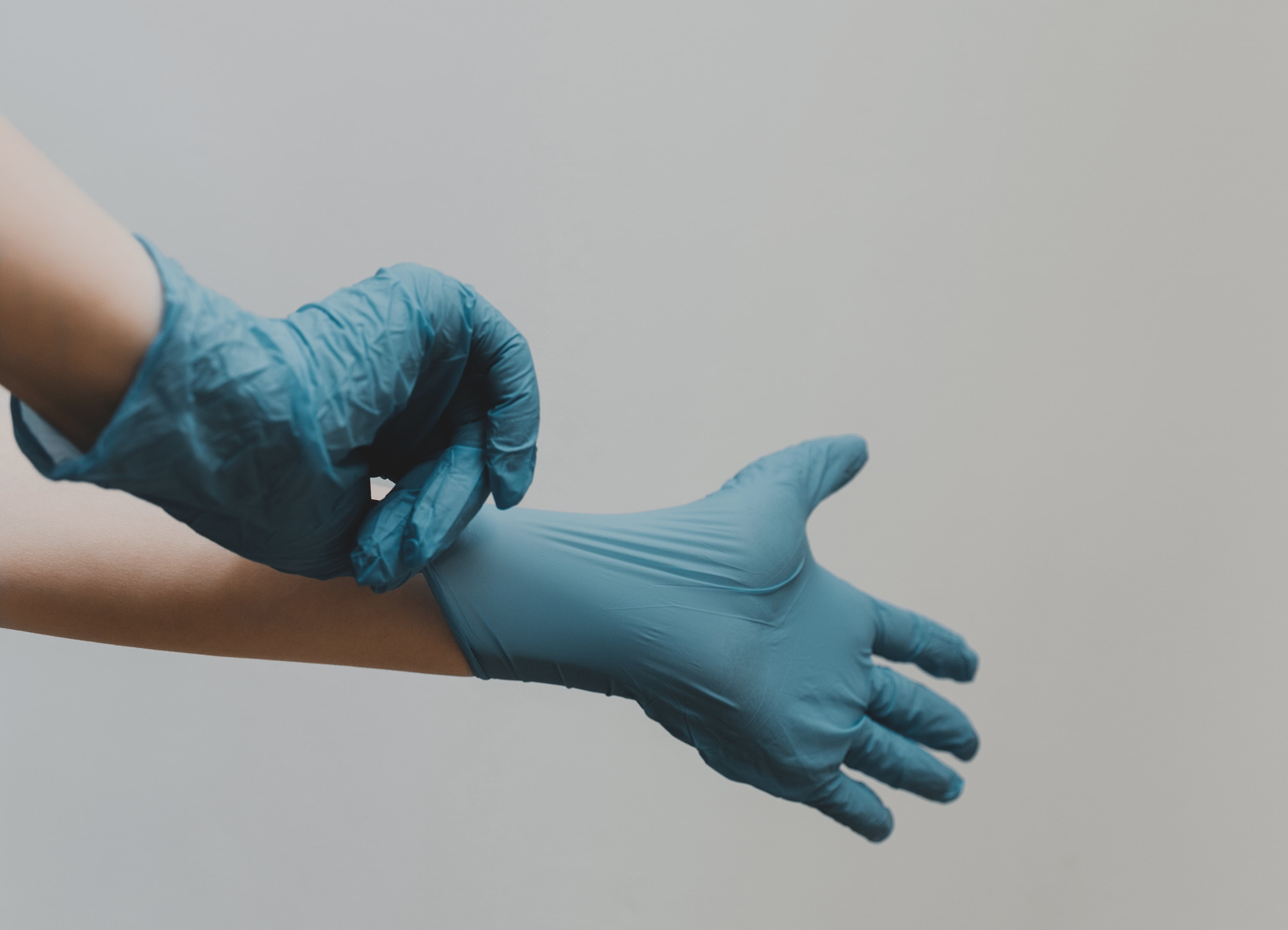 A pair of Caucasian hands pulling on blue medical gloves. The background is off white