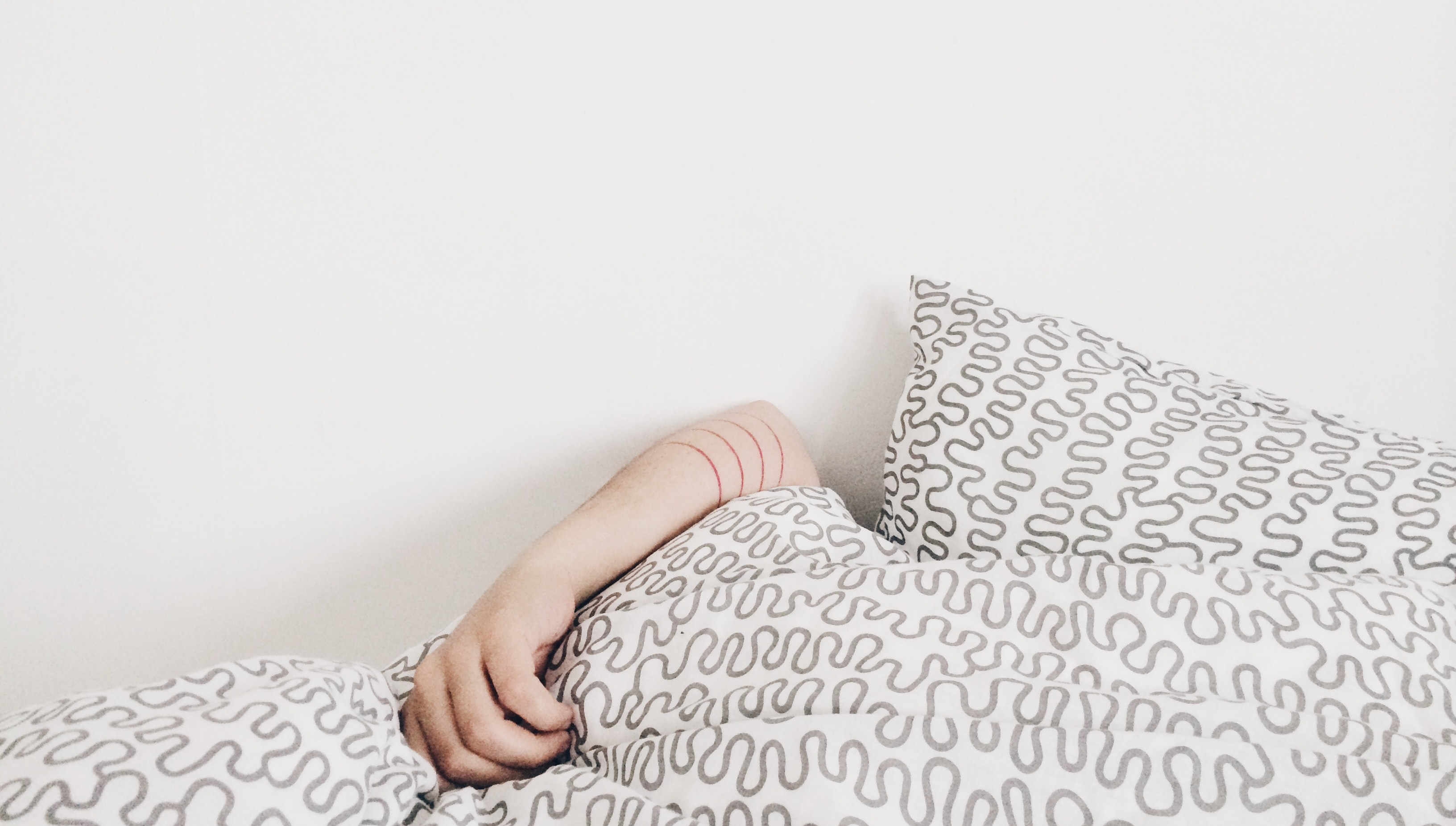 A white bedspread with grey squiggles, in front of a white wall. There is a Caucasian person's arm coming out of the bed spread.
