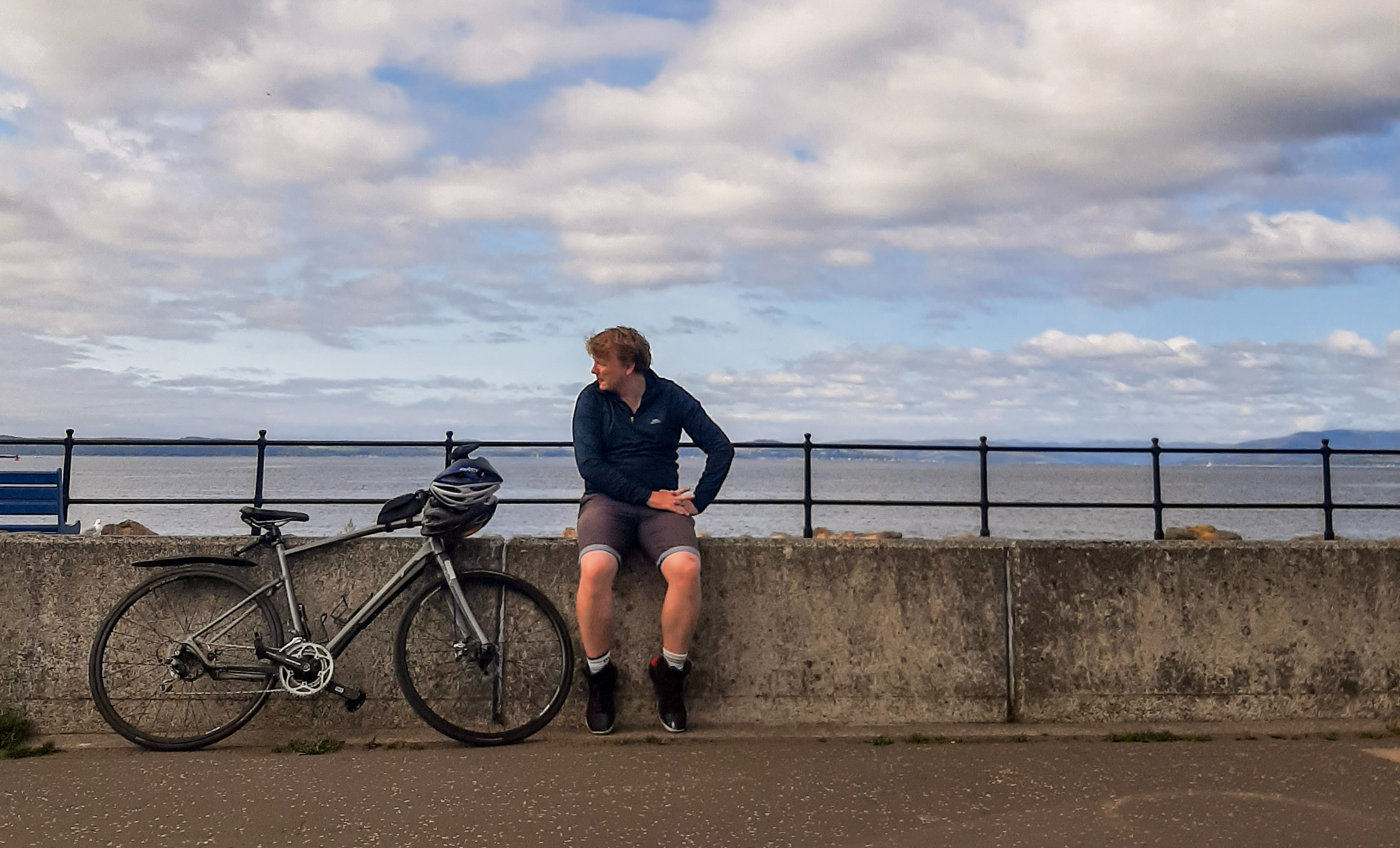 Rory is wearing a dark blbue jacket and shorts, and is sat on a concrete sea wall. To this left is a black bike, and the sea and sky are blue and white behind him.