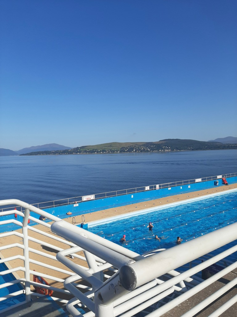 A clear blue sky with green hills in the back. In the foreground is the artificial blue pool of the Gourock Lido