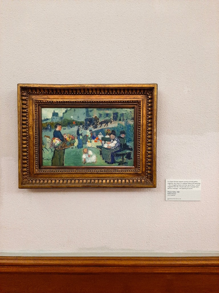A cream wall with a gold framed Picasso - the scene is of people in a garden