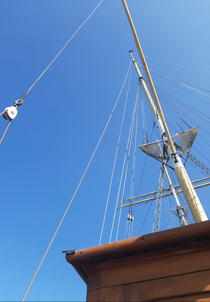 The mast of the Glenlee poking through the clear blue sky