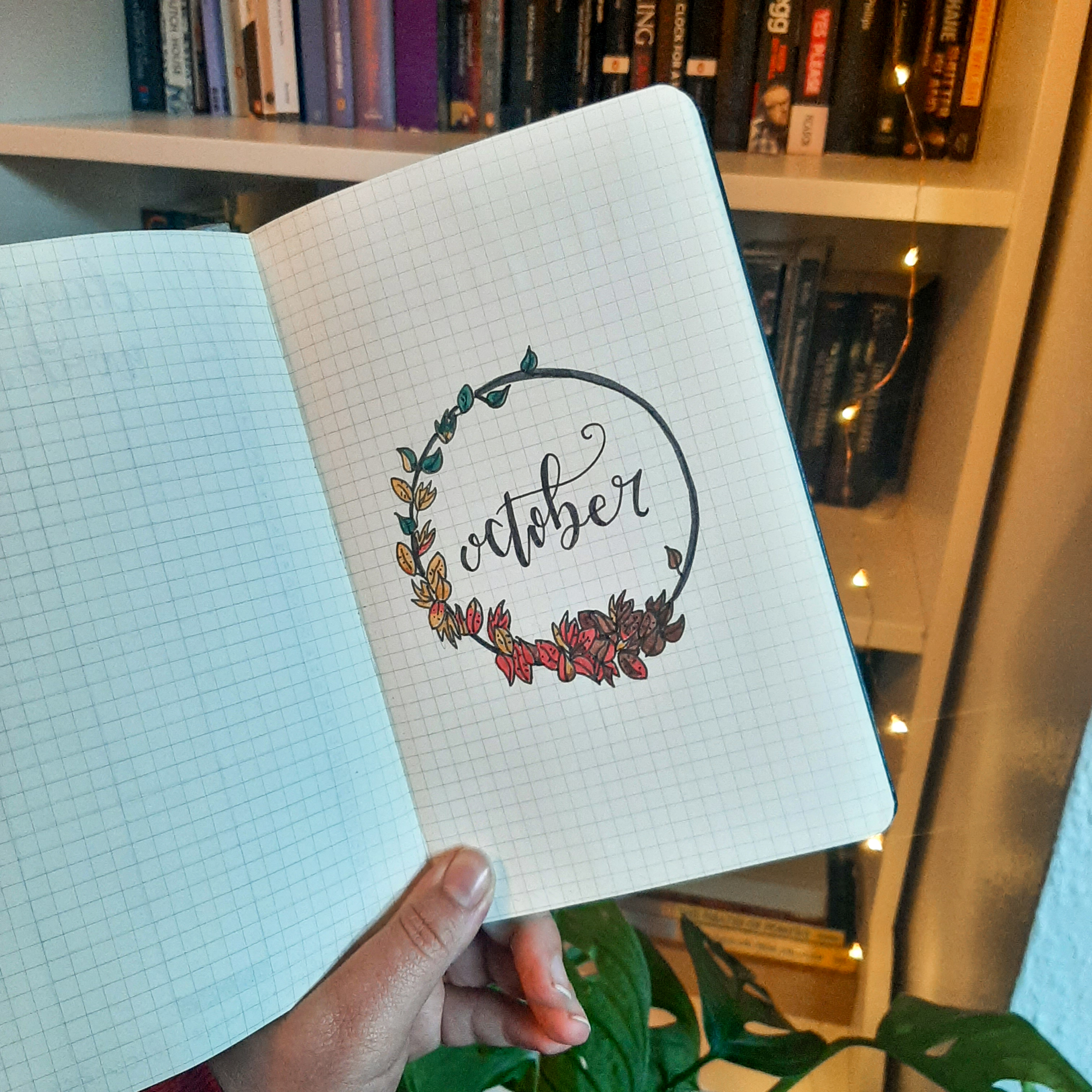 A picture of Rosie's bujo for October. The page has a black circle surrounded by leaves, with cursive 'October' written in the middle. It is held up in front of a bookcase, fairylights, and a monstera