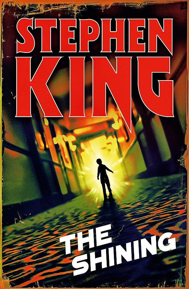 The cover of The Shining: Halloween edition. A blacked out figure of a child walks down the orange tinged carpeted corridor of the Overlook Hotel.